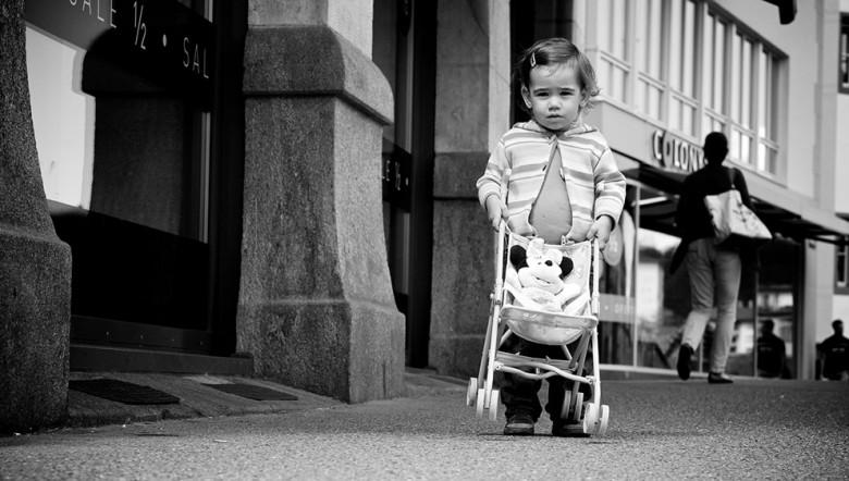 Lille pige går med klapvogn
